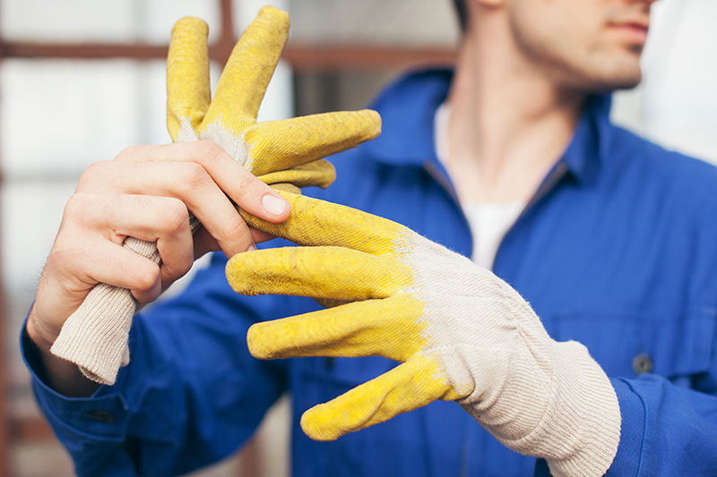 Caucasian builder taking off yellow protective gloves.